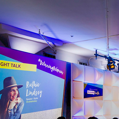 photo: woman presenting on stage with background graphics at corporate event