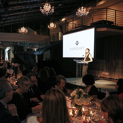 photo: woman presenting on stage at seating corporate dinner