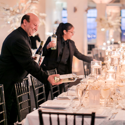 photo: waiters pouring wine at elegant table prior to event