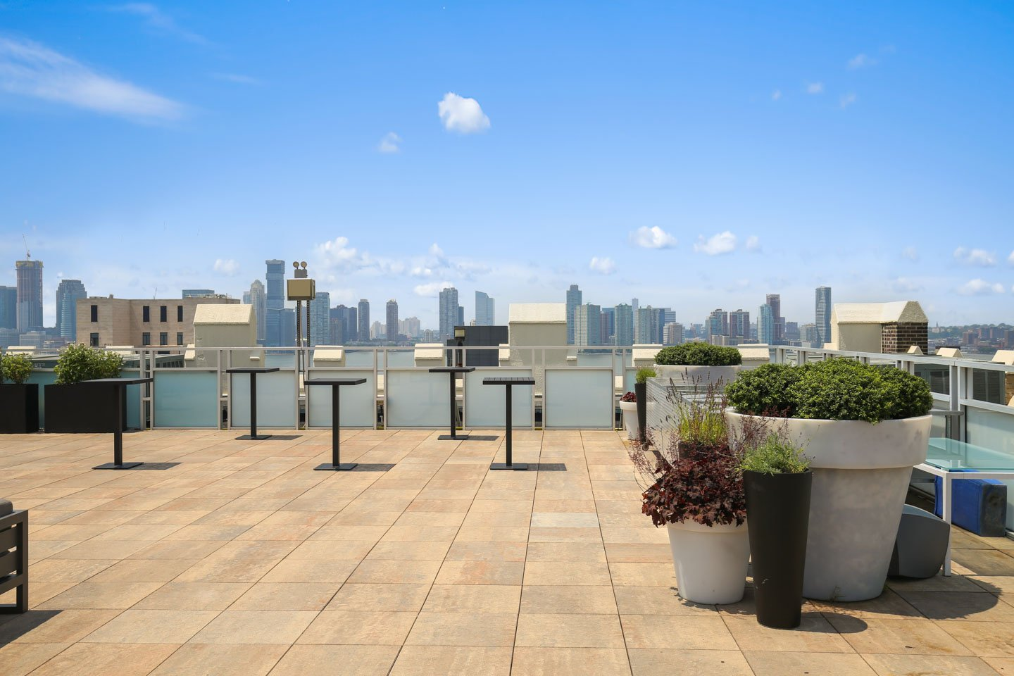 photo: rooftop cocktail space with tables and manhattan views